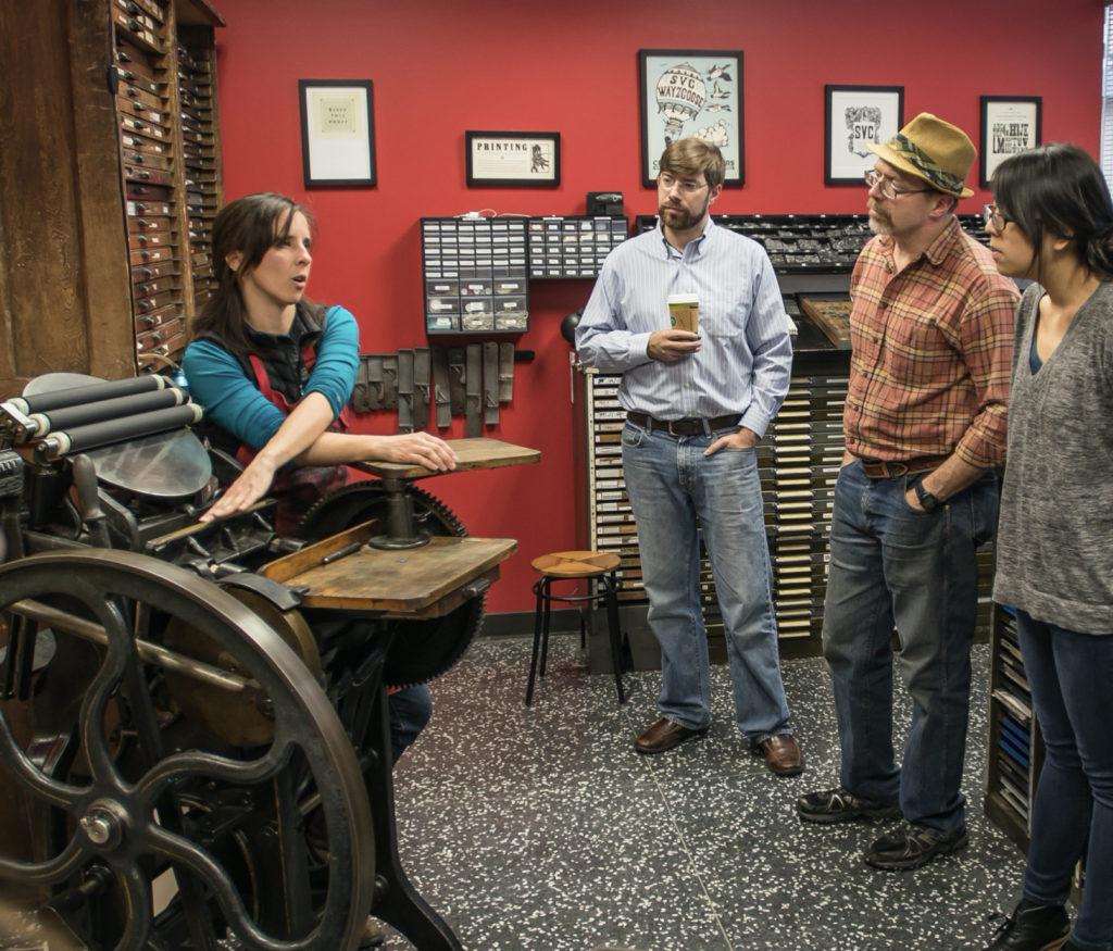 Instructor Amy Redmond introduces an 8x12 C&P platen press to students in SVC's Seattle letterpress studio.