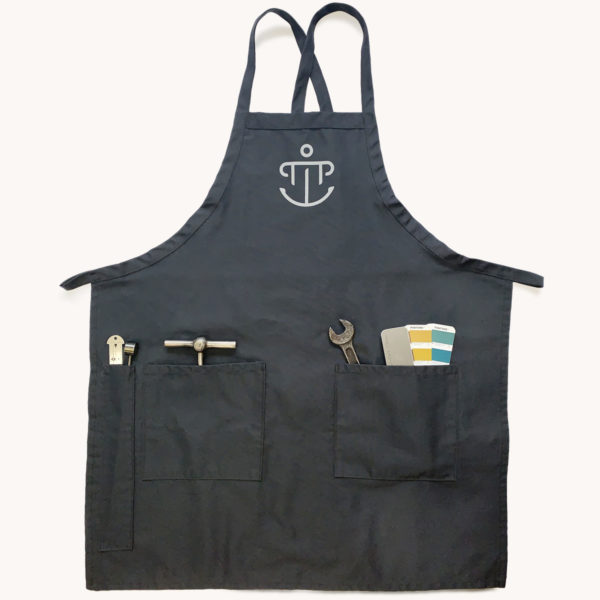 Partners in Print charcoal gray printer's apron features PiP's logo and 3 pockets for letterpress tools.